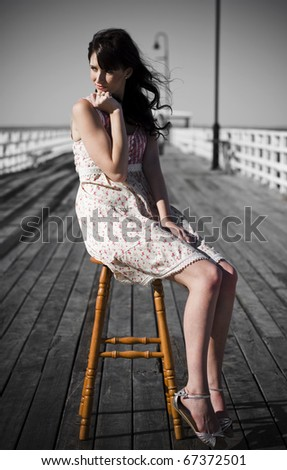 Pondering Pier Lady Sits And Ponders In A Moment Of Reflection On A Beach Pier - stock photo