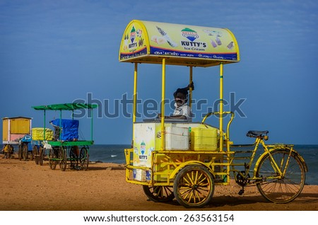PONDICHERRY, INDIA - FEBRUARY 12, 2013: Unidentified Indian street ice cream vendor with cart on beach - stock photo