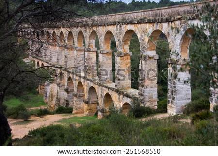 Pont del Diable (Pont de les Ferreres) of Roman Aqueduct, built in 27 BC - 14 AD, Tarragona, Spain, a UNESCO site - stock photo