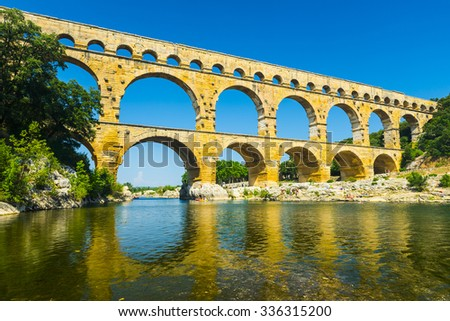 Pont du Gard is an old Roman aqueduct, southern France near Avignon. Reflection in the river Gard - stock photo