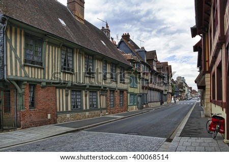 PONT-L'EVEQUE, FRANCE - JULY 8, 2005: Pont-l'Eveque (Calvados, Normandy, France): typical old street with a bicycle