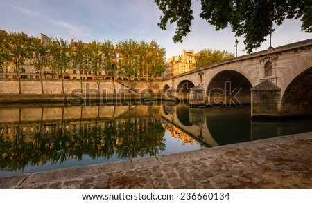 Pont Marie, a Paris bridge spanning the River Seine to the aspen tree lined bank on Ile Saint Louis. France Quiet early summer morning in the heart of Paris (4th arrondissement). - stock photo
