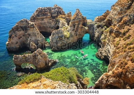 Ponta da Piedade - unique rock formation in the ocean - two boats with tourists visiting famous grottoes. Number one attraction in Lagos, Algrave, Portugal - stock photo
