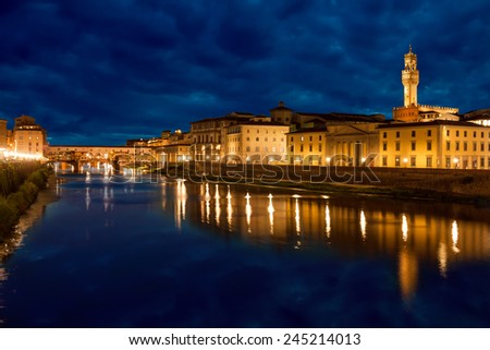 Ponte Vecchio and Palazzo Vecchio after sunset with reflections on Arno river, Florence, Italy