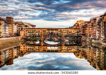Ponte Vecchio bridge in Florence, Italy. Arno River. Tuscany under sunset romantic sky, clouds - stock photo