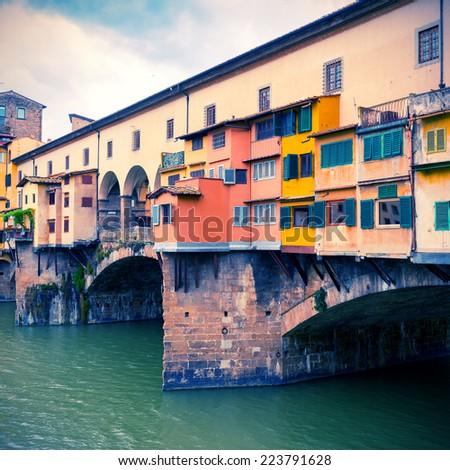 Ponte Vecchio over Arno river - famous old bridge in Florence, Italy. Vintage style photo. - stock photo