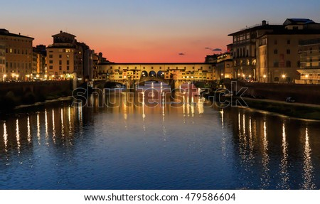 Ponte Vecchio - the oldest bridge of the city of Florence. River Arno, sunset, Tuscany, Italy, the reflection in the water.