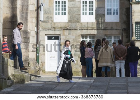 PONTEVEDRA, SPAIN - APRIL 2, 2015: A girl with costume of one of the brotherhoods to participate in a procession of Holy Week, running through the historic town.