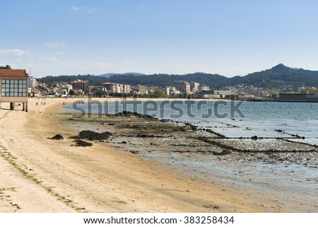 PONTEVEDRA, SPAIN - APRIL 12, 2015: People walking on the sand on a beach in Carril in the Ria de Arousa, clam farming area. - stock photo