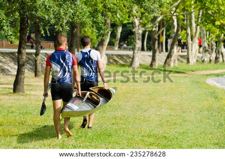 PONTEVEDRA, SPAIN - AUGUST 3, 2014: Extreme athletes carrying a canoe before participating  in the Spain Copa Canoe Marathon in Lerez River, to qualify for the World Championship. - stock photo