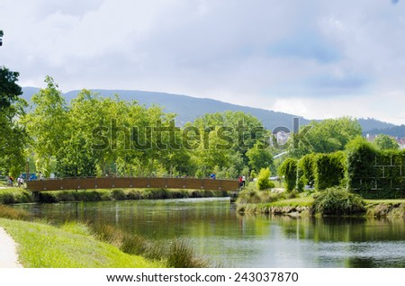 PONTEVEDRA, SPAIN - AUGUST 3, 2014: Many people walk through one of the wooden bridges, in one of city parks. - stock photo