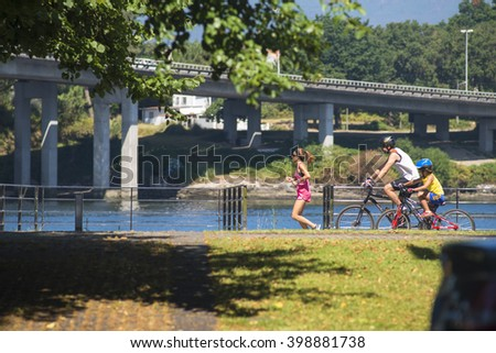 PONTEVEDRA, SPAIN - JUNE 28, 2015: A family cycling and running, enjoy along a street near the river that runs through the city. - stock photo
