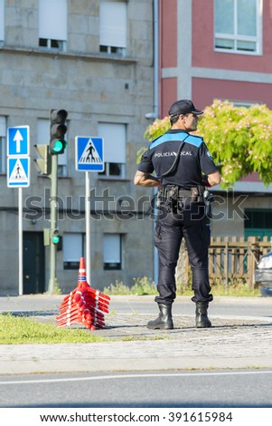 PONTEVEDRA, SPAIN - JUNE 20, 2015: A member of the local police controls traffic on a city street. - stock photo
