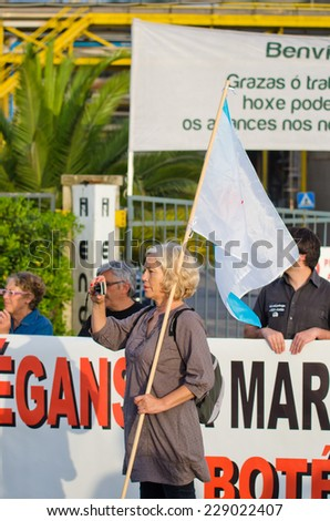 PONTEVEDRA, SPAIN - JUNE 21, 2014: A woman holding a flag of Galicia during a ecological demonstration against the permanence of paper pulp industry in the Ria de Pontevedra.
