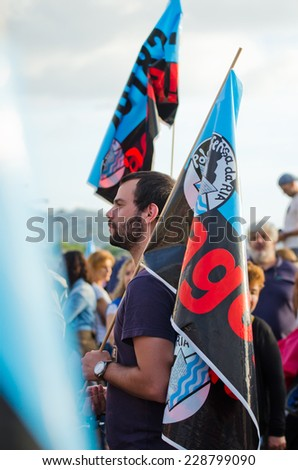 PONTEVEDRA, SPAIN - JUNE 21, 2014: A young man with a beard carrying a flag in a  ecological demonstration against the permanence of paper pulp industry in the Ria de Pontevedra.