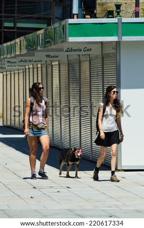 PONTEVEDRA, SPAIN - JUNE 14, 2014: Two young girls with glasses, also accompanied by a dog with glasses, walking down the street. - stock photo