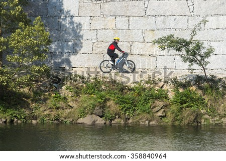 PONTEVEDRA, SPAIN - MARCH 15, 2015: A man, on a mountain bike, walking a path beside a river in one of the city parks. - stock photo