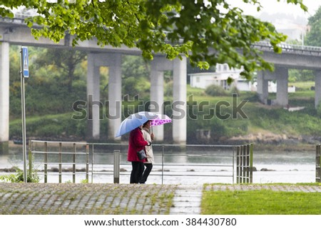 PONTEVEDRA, SPAIN - MAY 1, 2015: Two women with umbrella walking down the street in the rain, the walk along the river that runs through town. - stock photo
