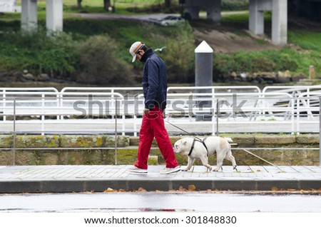 PONTEVEDRA, SPAIN - NOVEMBER 23, 2014: A young man with his dog, walk the promenade near the river which crosses the city. - stock photo