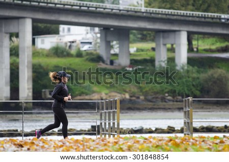 PONTEVEDRA, SPAIN - NOVEMBER 23, 2014: A young woman practicing running along the promenade near the river which crosses the city. - stock photo