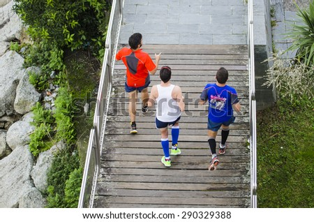 PONTEVEDRA, SPAIN - OCTOBER 19, 2014: Three men practice running on a boardwalk, at one of the banks of the river which crosses the city. - stock photo