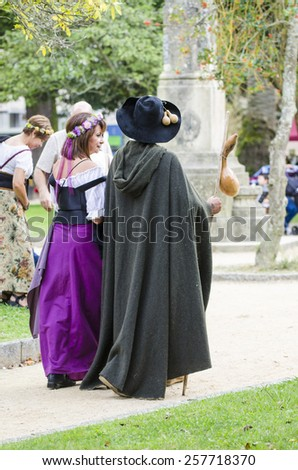 PONTEVEDRA, SPAIN - SEPTEMBER 6, 2014: A couple strolls, dressed in costumes of the Middle Ages, in medieval festival held each year in the historical district of the city. - stock photo