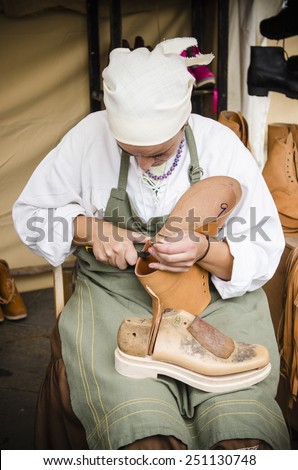 PONTEVEDRA, SPAIN - SEPTEMBER 6, 2014: A shoemaker manufactures boots, in medieval festival held each year in the historical district of the city.