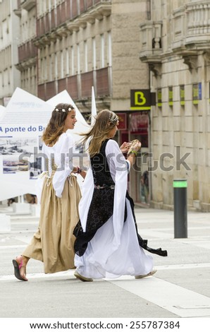 PONTEVEDRA, SPAIN - SEPTEMBER 6, 2014: A young girls walking, dressed in colorful costumes of the Middle Ages, in medieval festival held each year in the historical district of the city. - stock photo