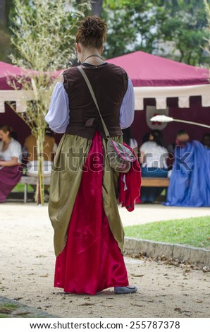 PONTEVEDRA, SPAIN - SEPTEMBER 6, 2014: A young woman in costume of the Middle Ages, in medieval festival held each year in the historical district of the city. - stock photo