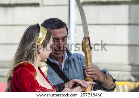 PONTEVEDRA, SPAIN - SEPTEMBER 6, 2014: An archer instructs a woman to shoot with bow, dressed in costumes of the Middle Ages, in medieval festival  in the historical district of the city. - stock photo