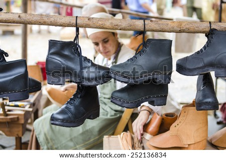 PONTEVEDRA, SPAIN - SEPTEMBER 6, 2014: Stall selling handmade boots, in medieval festival held each year in the historical district of the city. - stock photo
