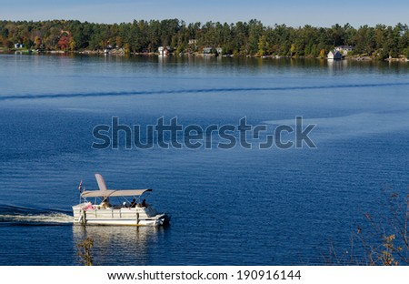 Pontoon boat on a blue lake - stock photo