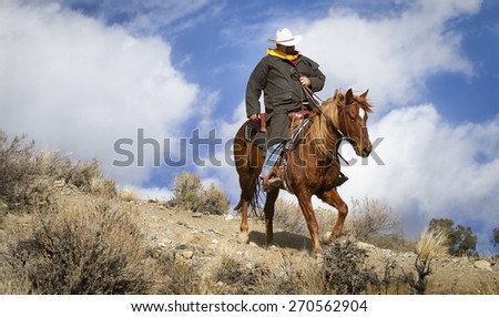 Pony Express Ridge Rider 1 in Color.  A lone cowboy in a black coat and white hat rides his horse down a mountain ridge with dramatic skies behind him. - stock photo
