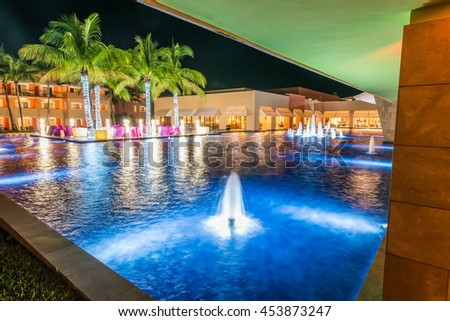 Pool at a luxury Caribbean, tropical resort at night, dawn time.