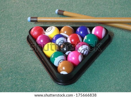 Pool balls on green cloth in triangle with cues - stock photo