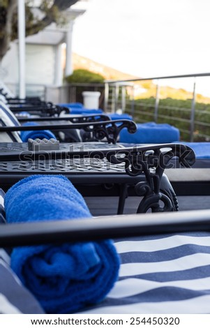pool chairs pool chairs by the pool with blue towels - stock photo
