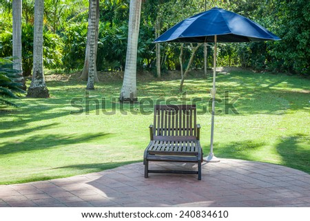 Pool chairs with umbrella in a relaxing setting - stock photo