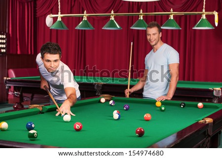 Pool game. Confident young man aiming the billiard ball with cue while his opponent  holding billiard cue and smiling on the background - stock photo