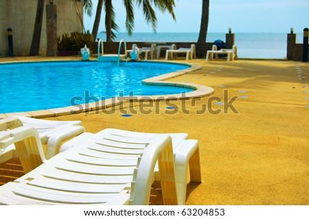 Pool near the beach in tropical resort. - stock photo