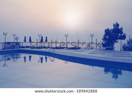 pool on background of sea and the setting sun - stock photo