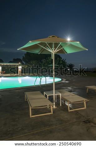 Pool, sunbeds and umbrellas at night. Night lights. Greece, Gythio - stock photo