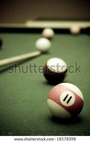 Pool table with a couple of balls and cue - stock photo