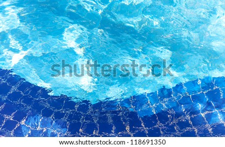 Pool water ripple background texture with bright reflections and blue tiles. - stock photo