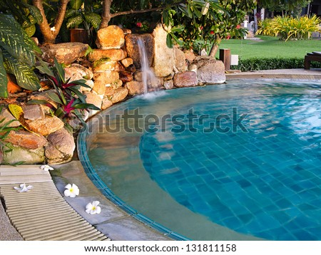 Pool with a waterfall in a resort - stock photo