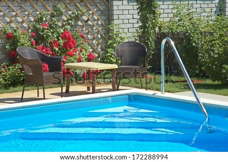 pool with lounge area and garden patio furniture - stock photo