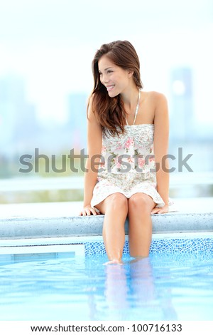Pool woman relaxing sitting in summer dress with legs in pool smiling happy with skyline in background. Beautiful mixed race Asian Chinese / Caucasian girl.