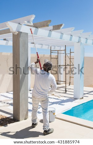 poolside villa pergola being painted white just after construction by a painter dressed in white, wearing a cap and using a roller with a long handle.