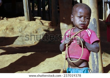 Poor african boy with a string - is he trying to attempt a suecide? - stock photo