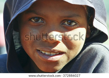 Poor African handsome boy with a hood on his head and half his face in shadow