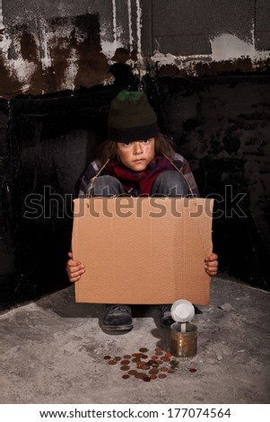 Poor beggar child on the street with coins on the ground and blank sign for copy space - stock photo